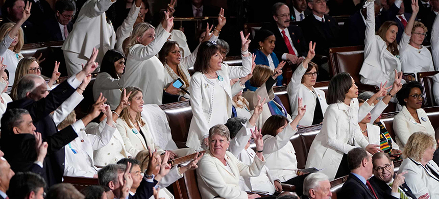 Female members of Congress wearing white, hold up three fingers for the HR3 health care bill as Donald Trump talks about healthcare during his State of the Union address. (photo: Joshua Roberts/Reuters)