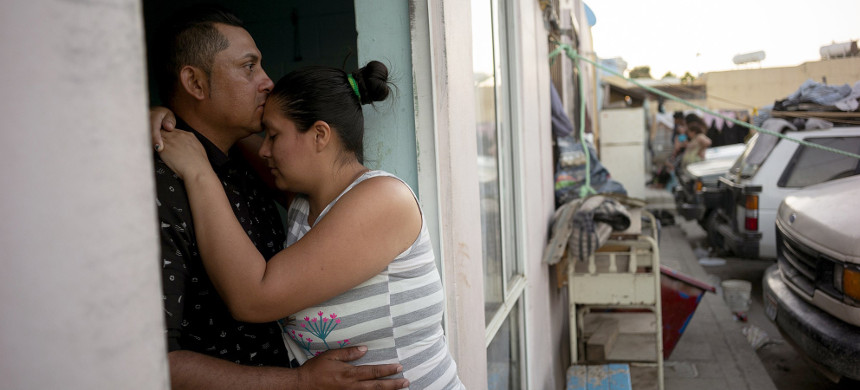 Juan Carlos Perla embraces his wife, Ruth Aracely Montoya, in the entrance to their home in Tijuana, Mexico, on June 19, 2019. The Perla family of El Salvador has slipped into a daily rhythm in Mexico while they wait for the U.S. to decide whether they will win asylum. A modest home replaced the tent they lived in at a migrant shelter. (photo: Gregory Bull/AP)