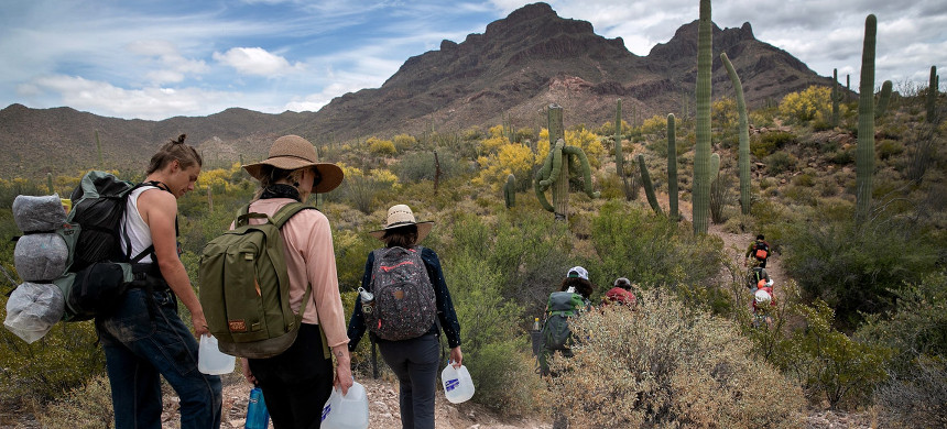 Volunteers with humanitarian aid organization No More Deaths walk with jugs of water for undocumented immigrants on May 10, 2019, near Ajo, Arizona. (photo: John Moore/Getty)