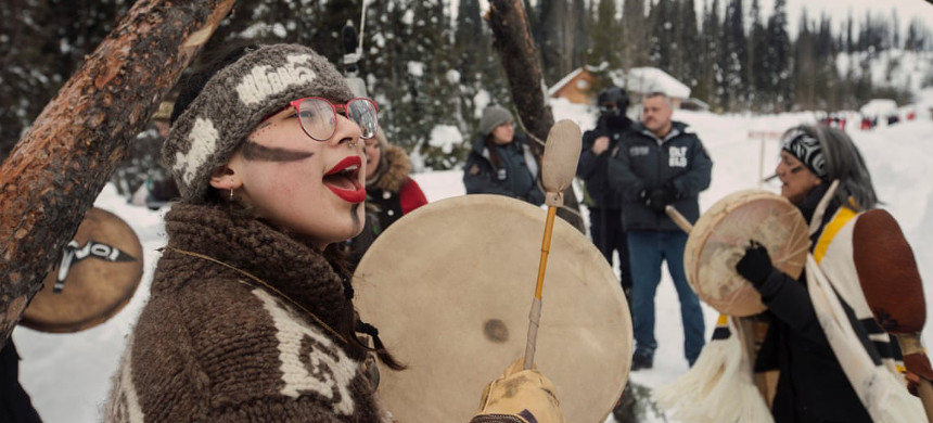 People stand in ceremony as police arrive to enforce Coastal GasLink's injunction at Unist'ot'en Healing Centre near Houston, British Columbia, on Monday. (photo: Amber Bracken)