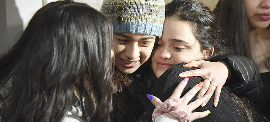 Meydi Guzman, right, a Crystal Lake Central High School senior who was in U.S. Immigration and Customs custody for several months, embraces friends as she is welcomed back at the home of school counselor Sara Huser on Thursday, Feb. 13, 2020, in Crystal Lake, Illinois. (photo: John Starks/Daily Herald/AP)