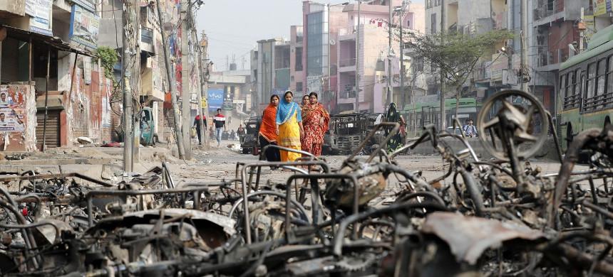 Women walk past charred vehicles Thursday in a riot-affected area of New Delhi following clashes over a new Indian citizenship law. (photo: Adnan Abidi/Reuters)