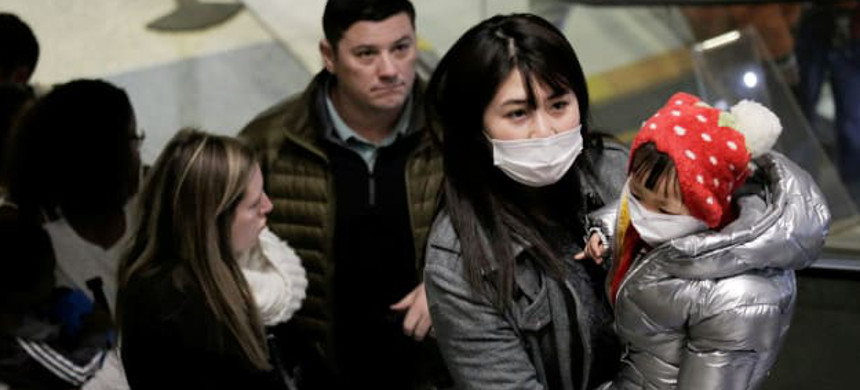 Travelers wearing masks arrive on a direct flight from China. (photo: David Ryder/Reuters)