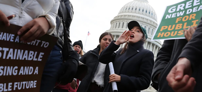 Rep. Alexandria Ocasio-Cortez (D-NY) chants with housing and environmental advocates before a news conference to introduce legislation to transform public housing as part of her Green New Deal outside the U.S. Capitol, Nov. 14, 2019, in Washington, D.C. (photo: Chip Somodevilla/Getty Images)