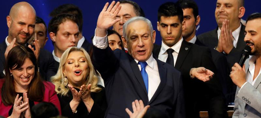 Prime Minister Benjamin Netanyahu stands next to his wife, Sara, following the exit poll announcement. (photo: Amir Cohen/Reuters)