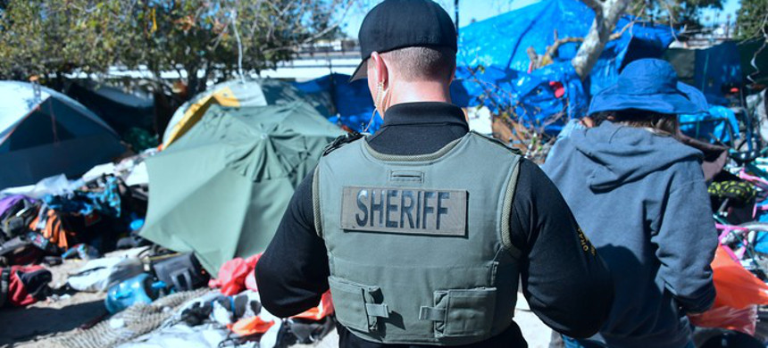 A Sheriff's officer and a social worker in a homeless encampment in Anaheim. (photo: Frederic Brown/Getty)