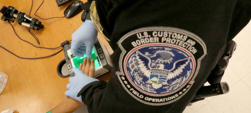 A woman seeking asylum has her fingerprints taken by a Customs and Border Protection patrol officer at a pedestrian port of entry from Mexico to the United States in McAllen, Texas, in May 2017. (photo: Carlos Barria/Reuters)