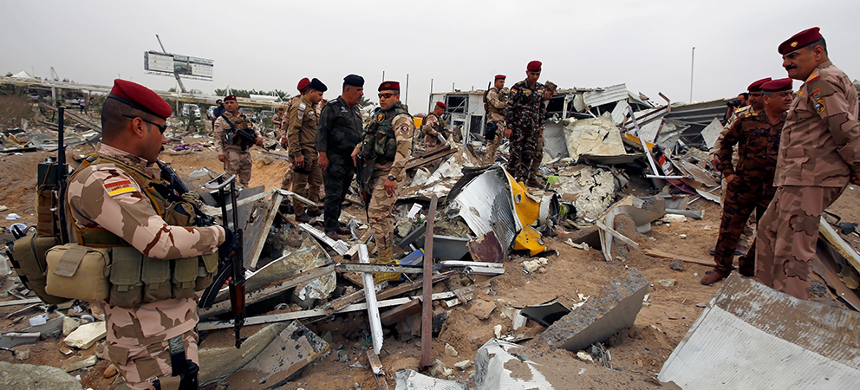 Members of Iraqi security forces inspect the damage at the airport hit by U.S. air strikes in Karbala. (photo: Alaa al-Marjani)