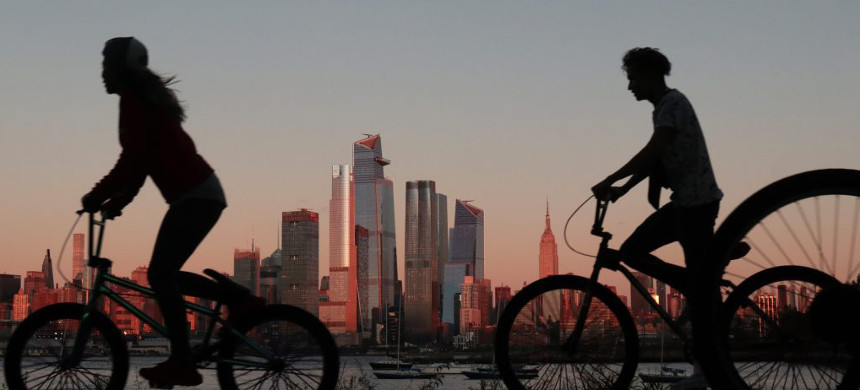 People ride their bicycles in front of the Empire State Building in New York City at sunset as seen from Hoboken, New Jersey (photo: Gary Hershorn/Getty)