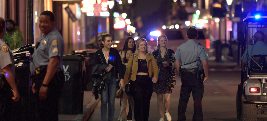 A group of young women walk past New Orleans police officers on Bourbon Street. (photo: Max Becherer/AP)