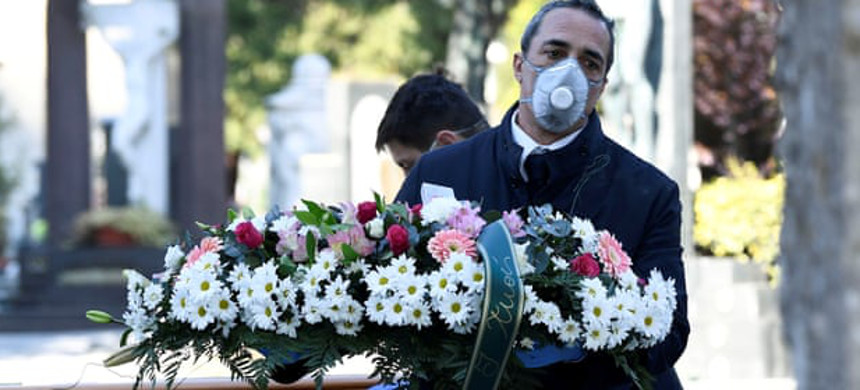 Funeral workers transport the coffin of a coronavirus victim into a cemetery in Bergamo. (photo: Flavio Lo Scalzo/Reuters)