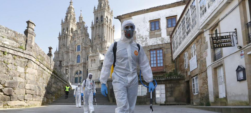 Military personnel in protective suits disinfect streets on Wednesday in Santiago de Compostela, Spain. (photo: Lavandeira/EPA)