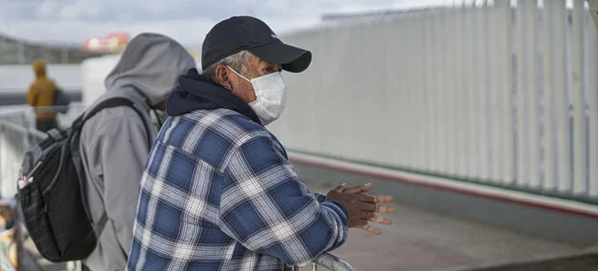 A Honduran migrant wears a mask while waiting in line to plead for asylum in Tijuana, Mexico. (photo: Sandy Huffaker/Getty Images)