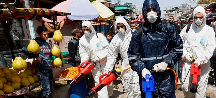 Workers wearing protective gear spray disinfectant as a precaution against the coronavirus, at the main market in Gaza City (photo: Adel Hana/AP)