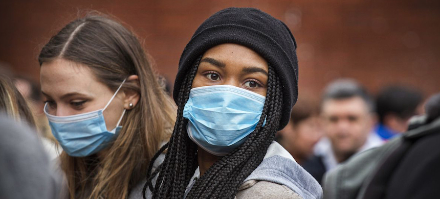 Young women wear face masks as protection against the coronavirus. (photo: Barry Lewis/In Pictures/Getty Images)