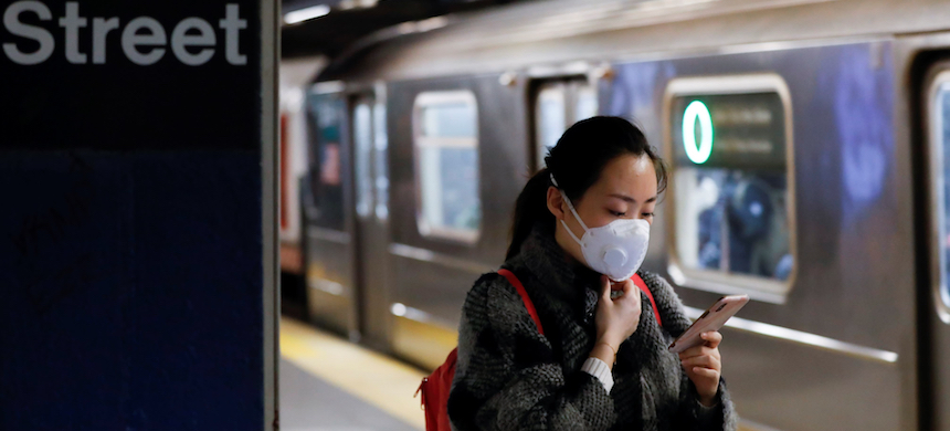 A masked woman waits for the subway in New York in early March. There have been scattered reports of racist attacks targeting Asians over the coronavirus. (photo: Reuters)