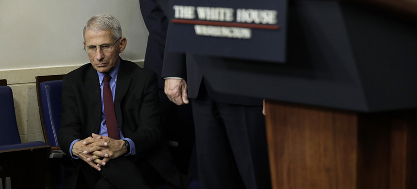 Dr. Anthony Fauci, director of the National Institute of Allergy and Infectious Diseases, listens as Trump speaks at a briefing on March 27. (photo: Yuri Gripas/Bloomberg/Getty Images)