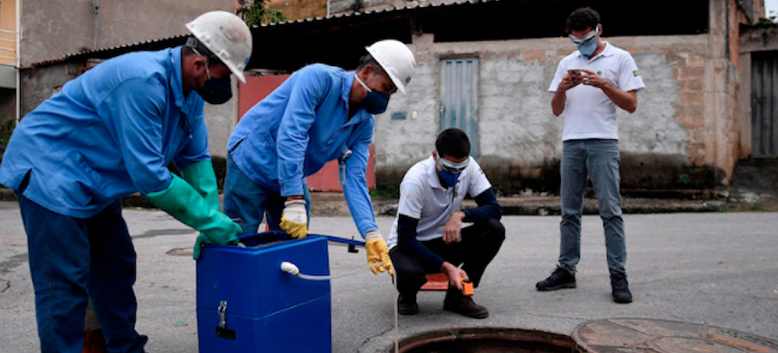 Researchers from Brazil's National Institute of Science and Technology and employees of the Minas Gerais Sanitation collect sewage samples to try to detect the coronavirus on April 16 in Belo Horizonte, Brazil. (photo: Douglas Magno/AFP/Getty Images)