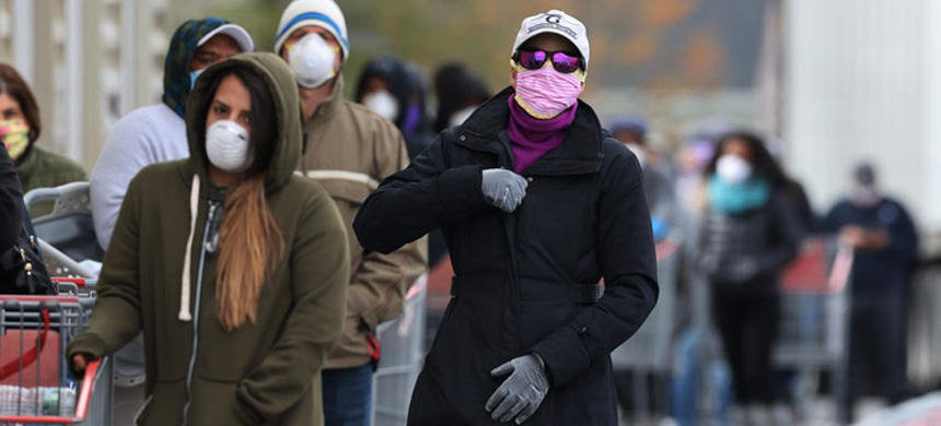 Customers wear face masks to prevent the spread of the novel coronavirus as they line up to enter a Costco Wholesale store April 16, 2020 in Wheaton, Maryland. (photo: Chip Somodevilla/Getty Images)