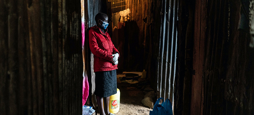 Rachael Mwikali of Coalition for Grassroots Human Rights Defenders Kenya waits in an alley during their food distribution to vulnerable families that have lost their income due to the novel coronavirus in Mathare slum, Nairobi, on April 25, 2020. (photo: Fredrik Lerneryd/AFP/Getty Images)