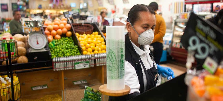 Esperanza Camargo, who works at a grocery store, poses for a portrait in her protective gloves and mask. (photo: William Camargo)
