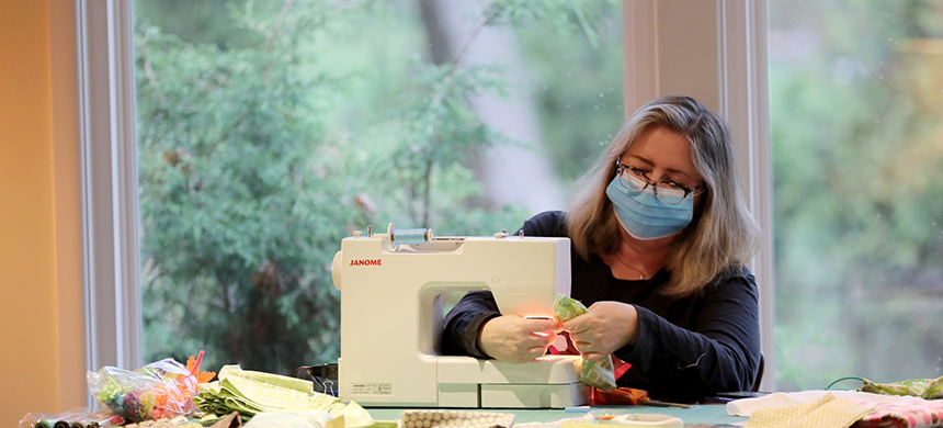 Kim Collins, co-founder of MommaArts Pregnancy Care Center, sewing masks in her home in South Orange, N.J. She is part of a 365-member Facebook group of sewing volunteers in South Orange and nearby Maplewood. (photo: Elsa/Getty Images)