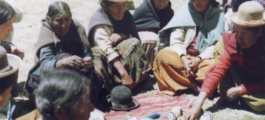 A meeting of Aymara mothers as part of ayllu reconstitution efforts in Ilata, Bolivia, 1985. The group is ritually sharing and chewing coca leaves, which are spread out in the center of the gathering. (photo: Andean Oral History Workshop)