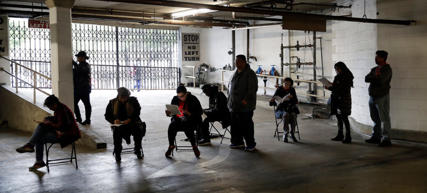 Workers lined up last week to apply for unemployment benefits at the Hospitality Training Academy in Los Angeles. (photo: Marcio Jose Sanchez/AP)
