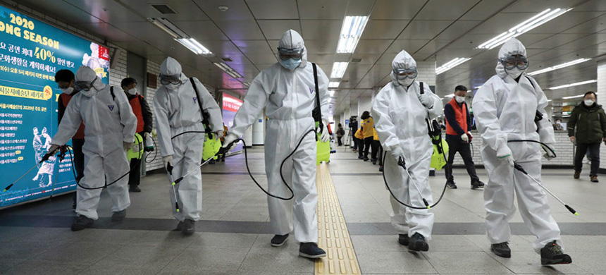 Workers in South Korea, which has been hit hard by COVID-19, disinfect a subway station in Seoul to slow the virus's spread. (photo: Newsis/AP)