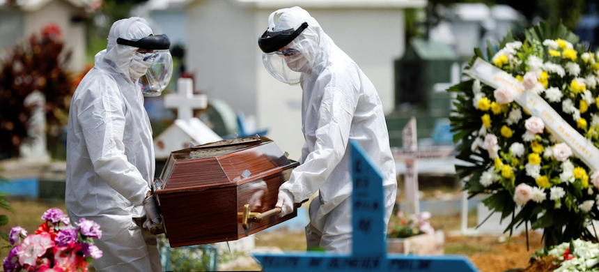 Gravediggers wearing protective suits carry the coffin of 68-year-old Natalina Cardoso Bandeira, who died after contracting coronavirus. (photo: Bruno Kelly/Reuters)
