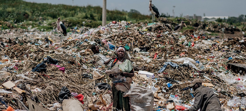 A woman takes a break from collecting waste to read the newspaper at the Dandora municipal dump site in Nairobi, Kenya, on Feb. 15, 2020. (photo: Khadija Farah/The Intercept)