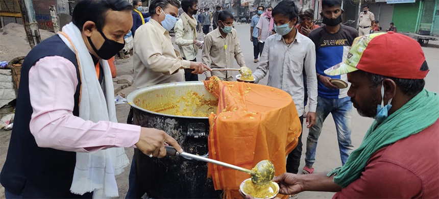 People eat free food distributed by local charities on April 14, 2020 in New Delhi, India. All shops and establishments in the market of Chandni Chowk are closed in a 40-day lockdown due to COVID-19. (photo: Pallava Bagla/Corbis/Getty Images)