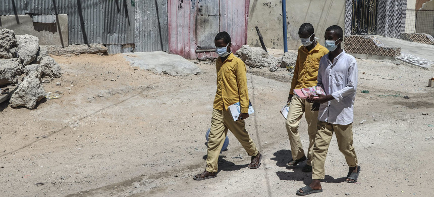 Students walk in a Mogadishu neighborhood in Somalia wearing face masks as protective measure against the novel coronavirus on March 19, 2020. (photo: Abdirazak Hussein/Getty)
