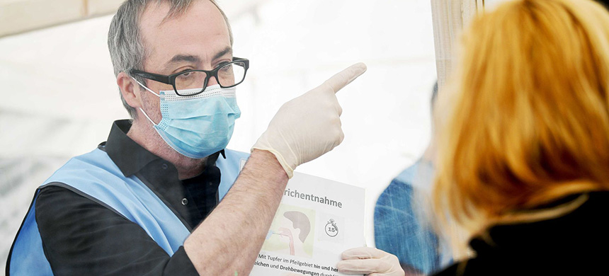 A health care worker explains how to carry out a coronavirus self-test in Berlin, Germany, on April 24. The country has considered giving residents who have recovered from Covid-19 'immunity passports' that would exempt them from stay-at-home measures. (photo: Britta Pedersen/Picture Alliance/Getty Images)
