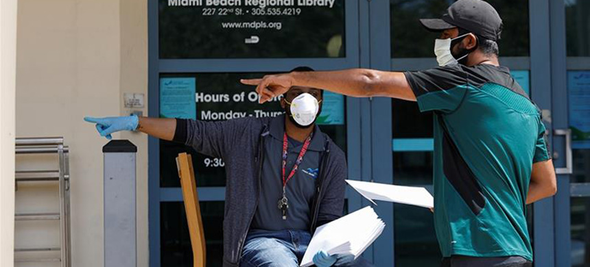 A man speaks with a library worker after receiving an unemployment form in Miami Beach, Florida. (photo: Marco Bello/Reuters)