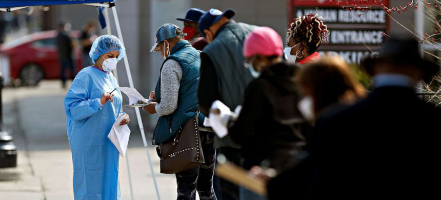 Chicago residents line up to get screened for COVID-19. (photo: Joshua Lott/Reuters)