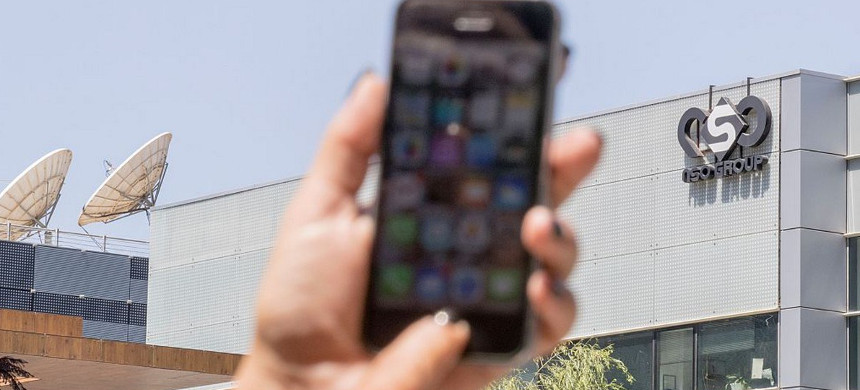 An Israeli woman uses her iPhone in front of the building housing the Israeli NSO group, in Herzliya, near Tel Aviv. (photo: Jack Guez/Getty)