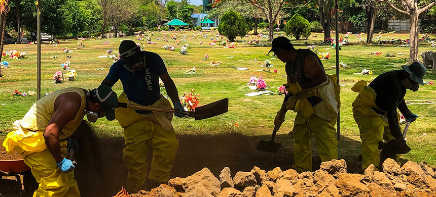 Gravediggers wearing suits and face masks to prevent the spread of the novel coronavirus bury a body Friday at the Jardínes del Recuerdo cemetery in Managua, Nicaragua. (photo: Inti Ocon/AFP/Getty Images)