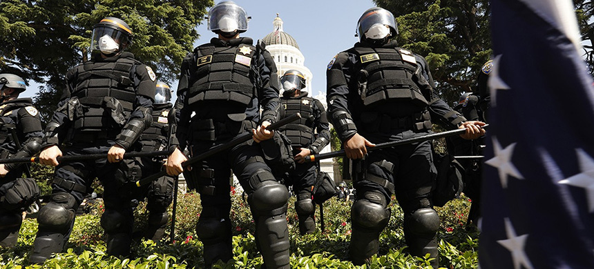 Officers wearing riot gear line the edge of the California state capitol grounds after removing protesters on May 1, 2020. (photo: Carolyn Cole/Los Angeles Times/Getty Images)