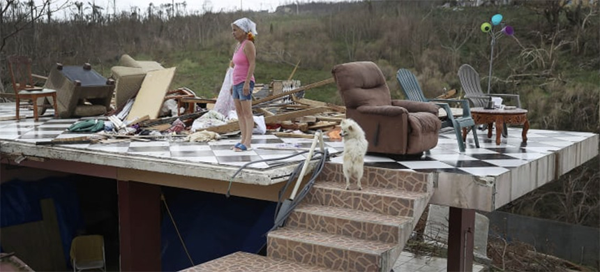 Irma Maldanado stands with Sussury her parrot and her dog in what is left of her home that was destroyed when Hurricane Maria passed through on September 27, 2017 in Corozal, Puerto Rico. (photo: Getty Images)