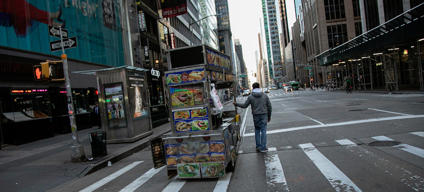 A food truck vendor pushes his cart down an empty street near Times Square in New York City. (photo: Wong Maye-E/AP)