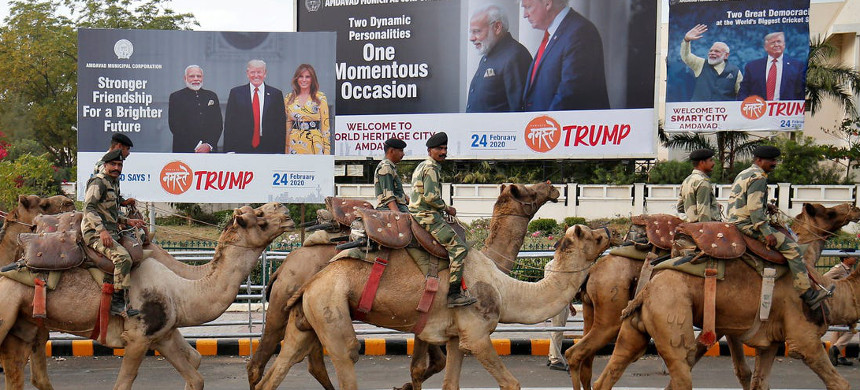 Indian soldiers ride camels past billboards featuring India's Prime Minister Narendra Modi, U.S. president Donald Trump and first lady Melania Trump. (photo: Reuters)
