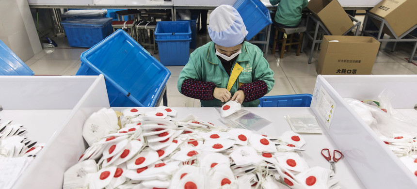 An employee works on the assembly line to make protective masks at a factory in Shanghai, China, on Jan. 31. (photo: Qilai Shen/Getty)