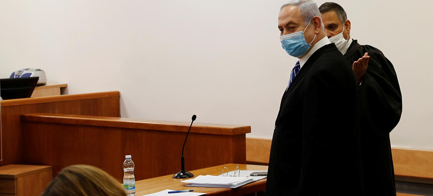Israeli prime minister Benjamin Netanyahu, wearing a face mask, stands inside the court room as his corruption trial opens at the Jerusalem District Court. (photo: Reuters)