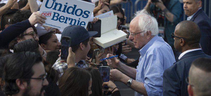 Sen. Bernie Sanders signs autographs at a February campaign event with Latino supporters in Santa Ana, California. (photo: Damian Dorvarganes/AP)