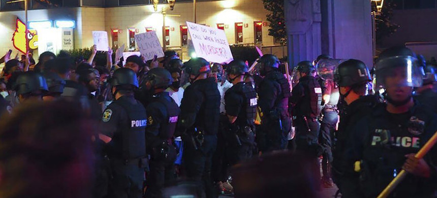 Police officers gathered Thursday in downtown Louisville, Kentucky, as protesters demonstrated against the killing of Breonna Taylor, a black woman fatally shot by police in her home in March. (photo: McKinley Moore/AP)
