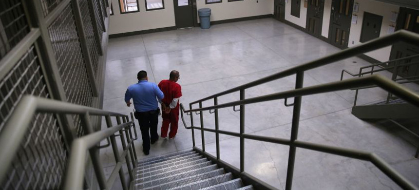 A guard escorts an immigrant detainee at the Adelanto ICE Processing Center in 2013. (photo: John Moore/Getty)