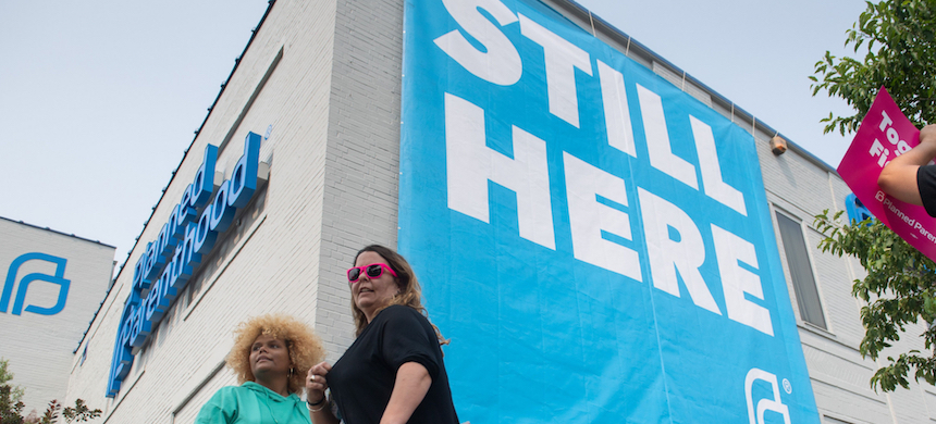A banner stating 'STILL HERE' hangs on the side of a Planned Parenthood building in St. Louis. (photo: Lawrence Bryant/Reuters)
