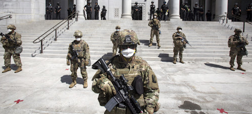 California National Guard troops stand in front of Los Angeles City Hall Sunday amid protests. (photo: BBC)