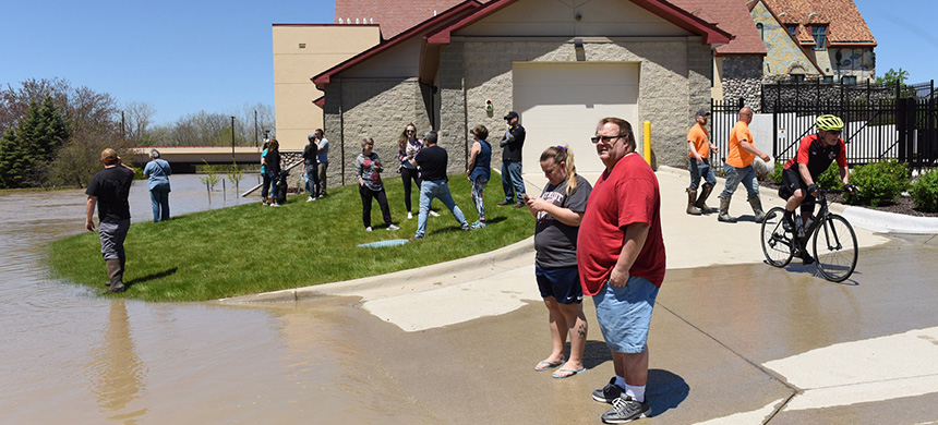 Crowds gathered in Midland, Michigan, to see the floodwaters as the Tittabawassee River rose. (photo: Emily Rose Bennett/NYT)